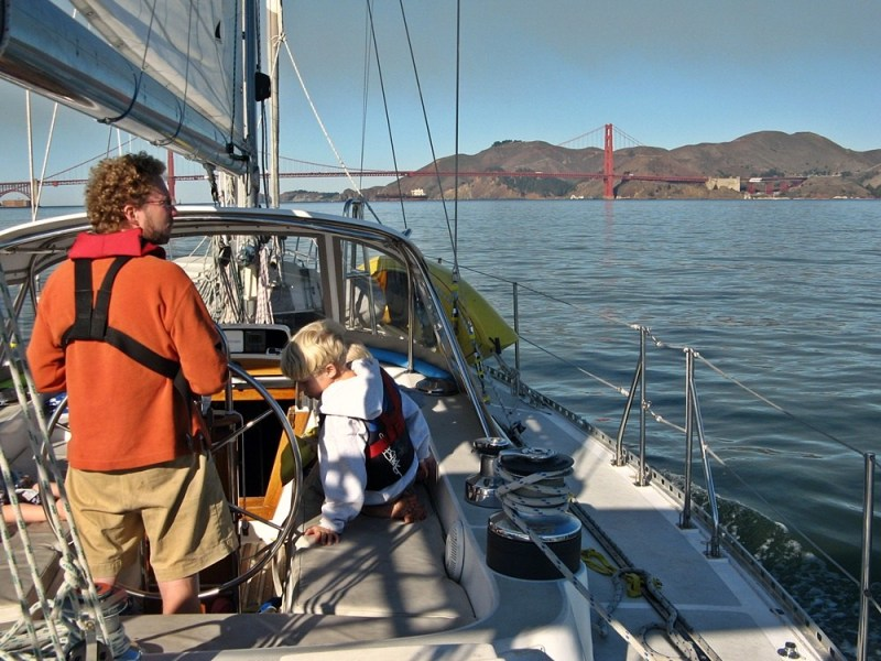 Looking forward from the rear of a sailboat: a man standing at the wheel steers toward San Francisco's Golden Gate Bridge, while a boy sits next to him in the cockpit.