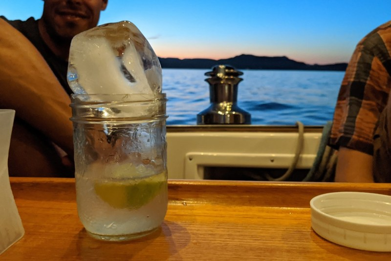 An oversized ice cube melts slowly into a cocktail glass, resting on a cockpit table at dusk.